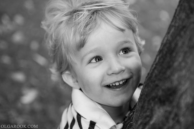 foto van een lachend jongetje die een boom omhelst