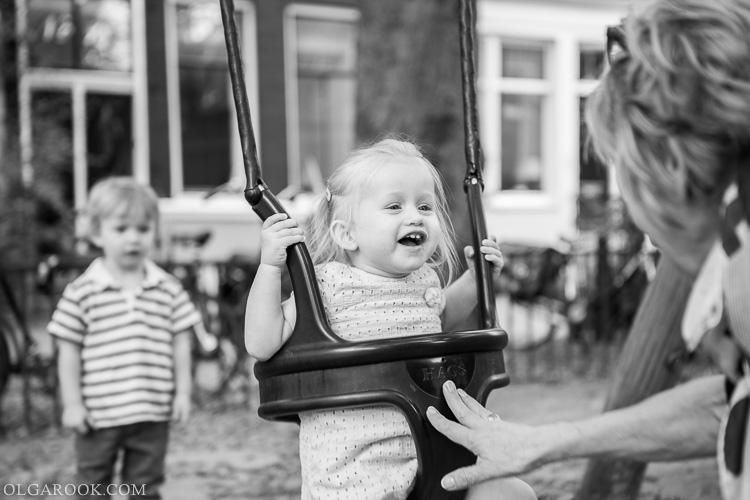 foto van een klein lachend meisje op een schommel