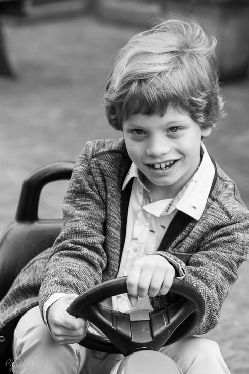 portrait of a laughing boy driving a pedal car