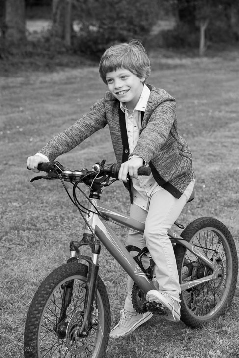 photo of a laughing little boy riding a bike