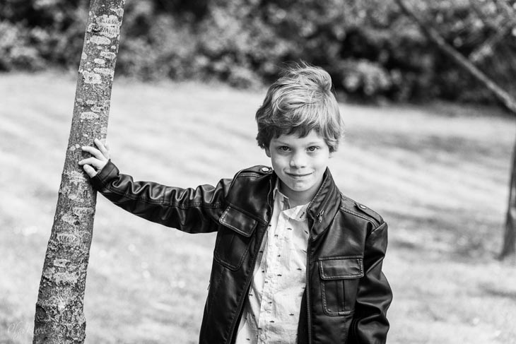 portrait of a boy standing at the edge of the wood