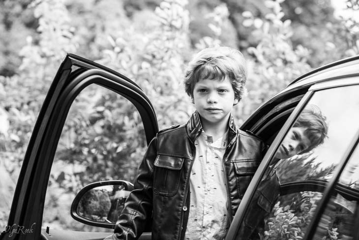 photo of a boy standing next to a car