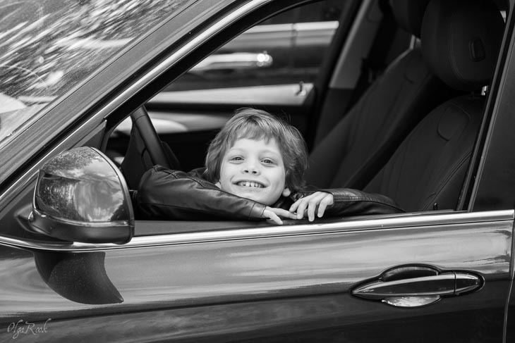 photo of a laughing little boy in a car