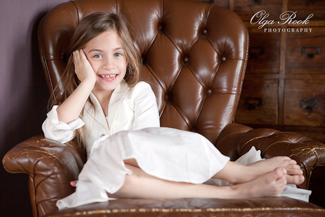 Portrait of a smiling and joyful little girl sitting in a big antique armchair.