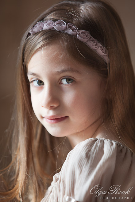 Closeup portrait of a pretty little girl with long hair. Beautiful warm light, almost chiaroscuro, adds a painterly effect to the image. The girl's hairstyle and dress give an exquisite antique feel.
