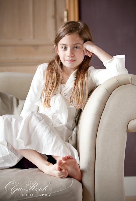 Portrait of little girl sitting on a sofa in a living room. She has long hair, wears a white dress and is barefoot.