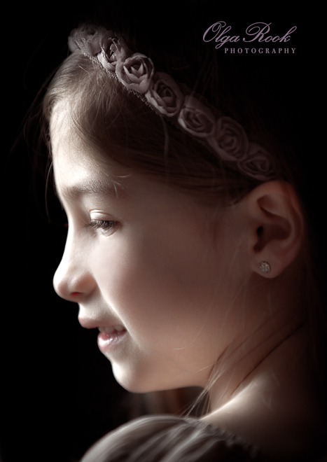 Artistic portrait of a little girl en profile, retro style. The lighting creates a chiaroscuro effect.