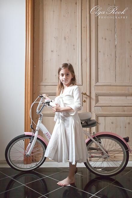 Retro-achtige foto van een klein meije met een fiets in de gang van een grote huis.