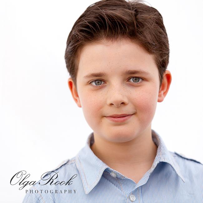 Portret van een lachend jongen met donkerblond haar.