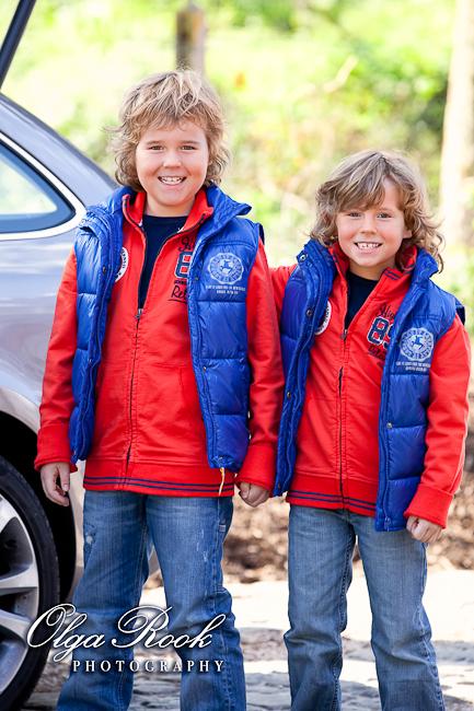 Foto van twee lachende broerjes die gelijke kleren dragen.