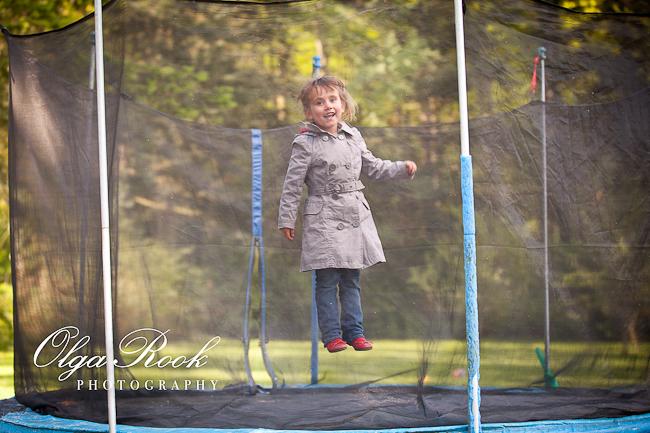 Foto van een klein meisje: springend en lachend.