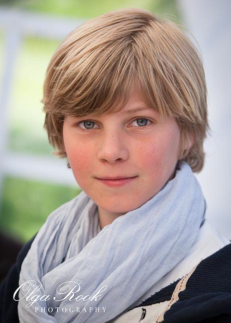 Een portret van een knappe blonde jongen met blauwe ogen.