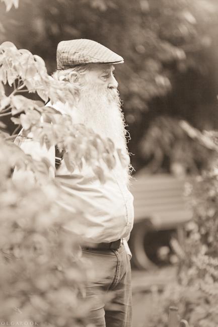 Een foto met een antieke sepia effect: een oude man met lange witte baard wandelend door de tuin.