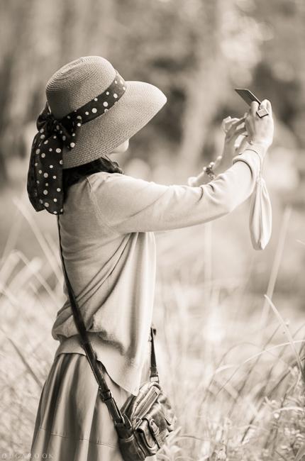 Foto van een elegante slanke dame met een mooi retroachtig zomerhoedje. Zij neemt foto's in de park.
