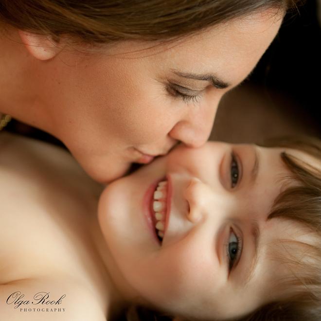 Warme kleurenportret van een moeder die haar kleine kindje een liefdevolle zoen op de wang geeft.