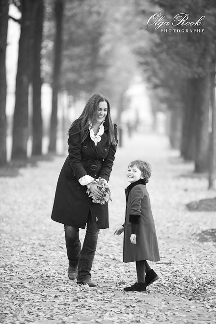 Foto van een vrouw en kind op een laan van een herfstpark. De vrouw houd herfstbladeren in haar handen en wil ze omhoog gooien.