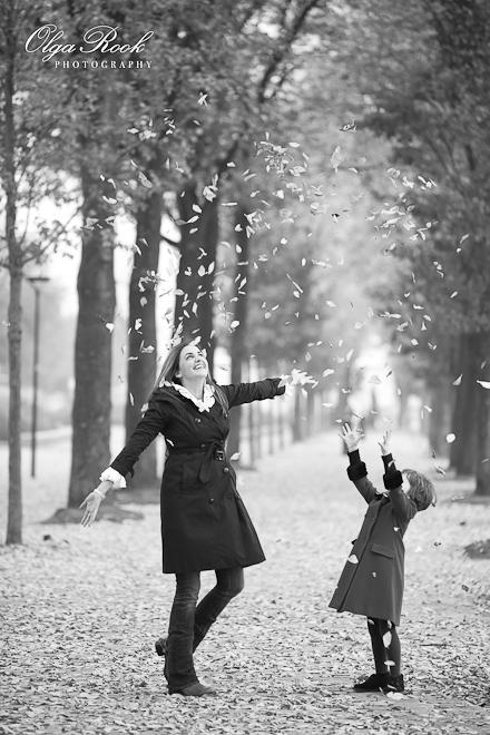 Foto van een moeder en kind die herfstbladeren in de lucht gooien.