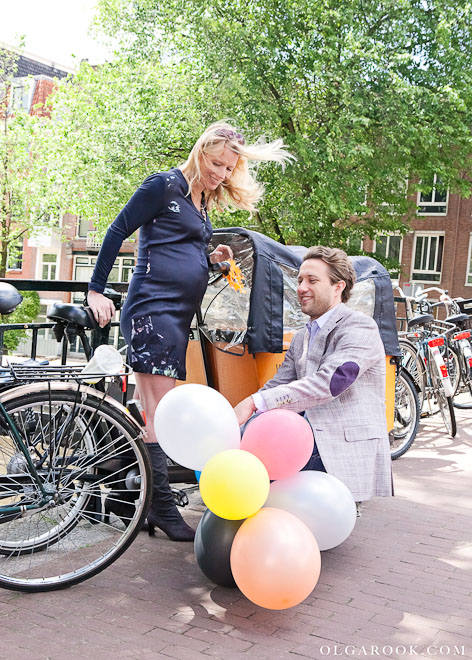 Photo of a couple: a beautiful pregnant young woman and a handsome guy with balloons on a bridge in Amsterdam.