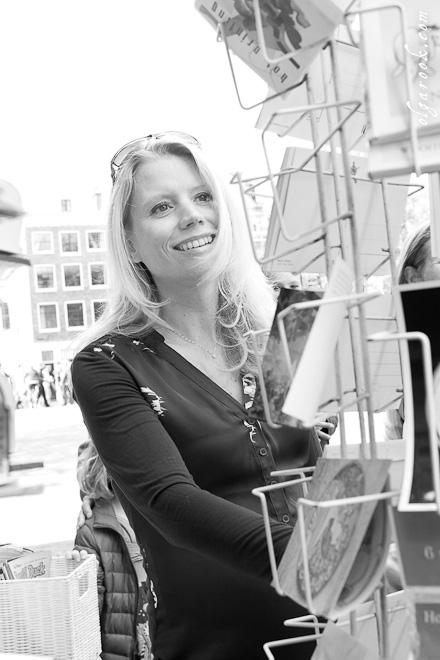 Foto van een mooie blondine die de wenskaarten in een winkeltje in Amsterdam bekijkt.