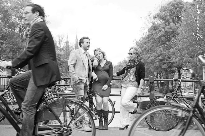 Familiefoto op een brug in Amsterdam met fietsers die voorbij rijden.