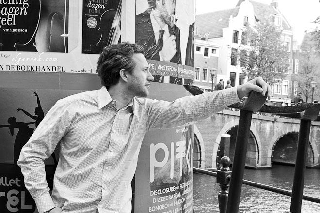 Artistieke portret van een jonge man op een gracht in Amsterdam.