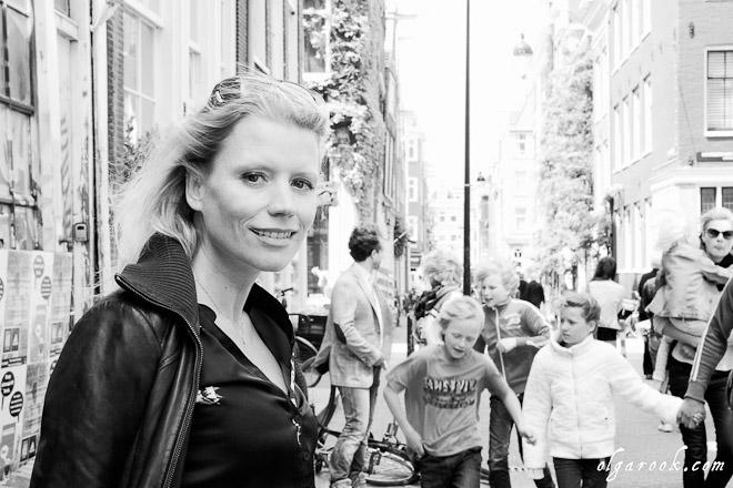 Portret van een blonde vrouw in het midden van een drukke straat in Amsterdam.