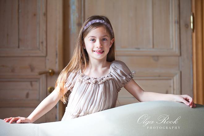 Foto van een klein meijse achter een bankstel. Zij draagt een mooie en elegante jurk.