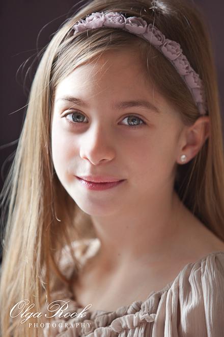 Foto van een mooie klein meisje. Zij lacht vriendelijk in de camera. De foto heeft warme zachte kleuren en lijkt op een antieke schilderij.