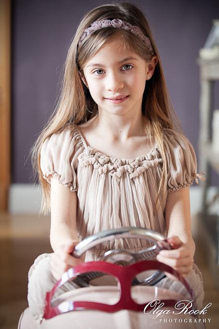 Portret van een lief klein meisje met lange haar, die achter de stuur van een speelgoedauto zit.