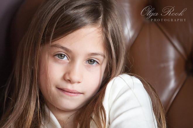 Closeup portret van een klein meisje op een antieke leunstoel.
