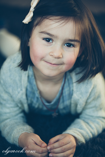 Nostalgisch vintage-achtig portret van een klein meisje met donkere haar en sprankelende ogen.
