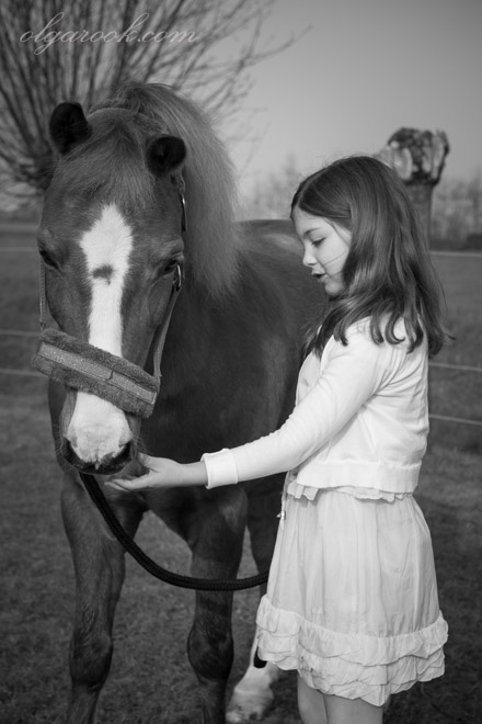 Nostalgic black and white photo of a little girl talking to her pony.