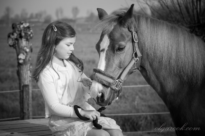 Dreamy and romantic photo of a little girl playing with her pony