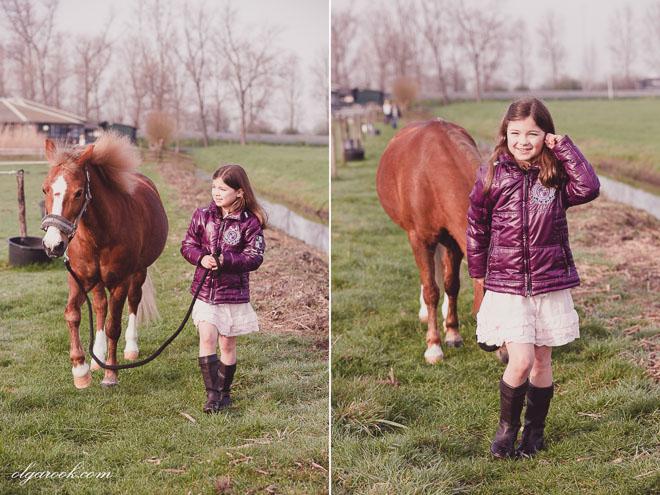 kleurenfoto's van een meisje die met een pony op een pad naast de stallen wandelt