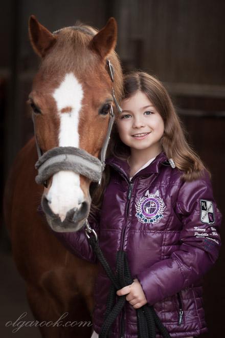 Kleurenportret van een klein meisje met een paard in de stal