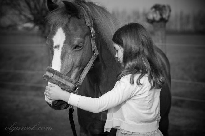 Nostalgisch en emotioneel portret van een klein meisje met haar pony