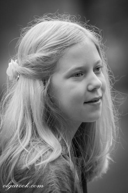 Zwart-wit portret van een blond meisje met een zacht dromerig glimlach