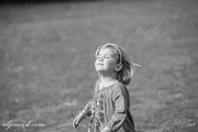 portrait of a little girl running through a field