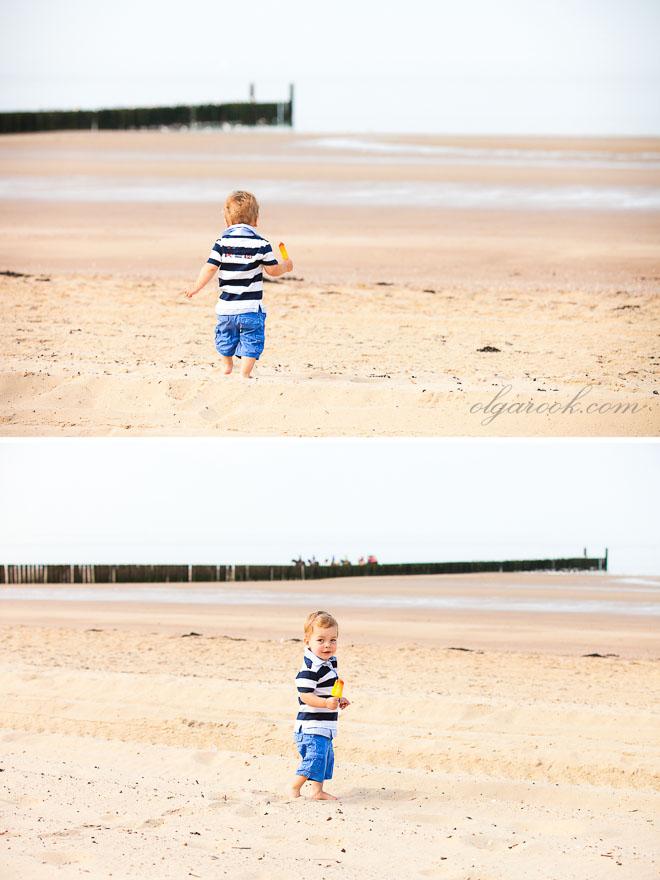 Foto van een klein jongetje met een ijsje op het strand