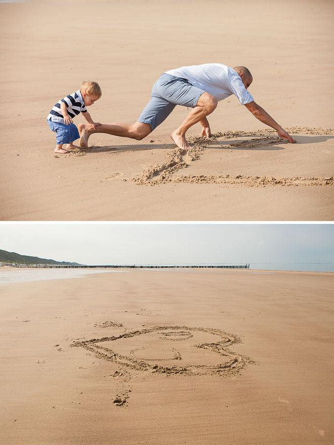 foto van een man die een grote hart op het zand tekent