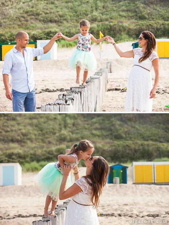 Foto van de ouders die hun dochtertje helpen op paaltjes op het strand te lopen
