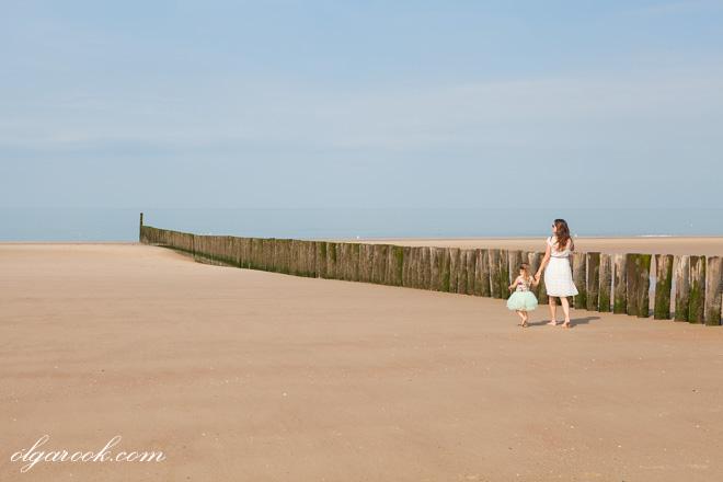 Foto van een moeder en haar dochtertje die langs een rij van paaltjes op het strand lopen. Het sfeer heeft iets van een schilderij van Salvador Dali.