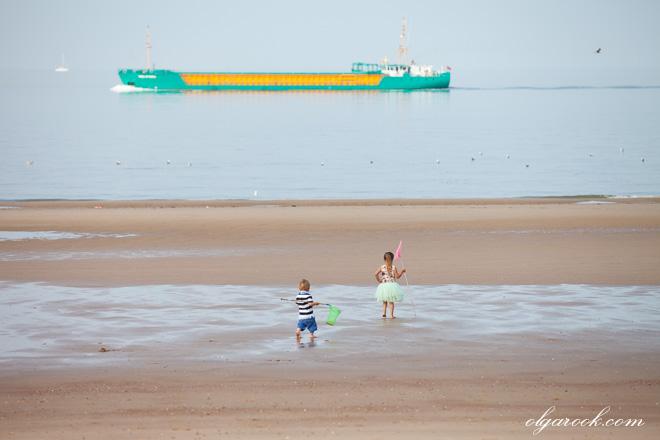 foto van twee kleine kinderen die bij de zee wandelen
