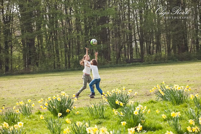 photo of two children playing ball in a park among the spring flowers