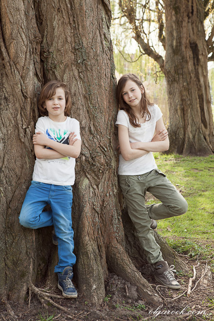 Portrait of a little brother and sister leaning against a tree in a park. Both children have a tough expression on their faces