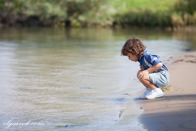 A dreamy photo of a little boy playing at a river bank next to the water