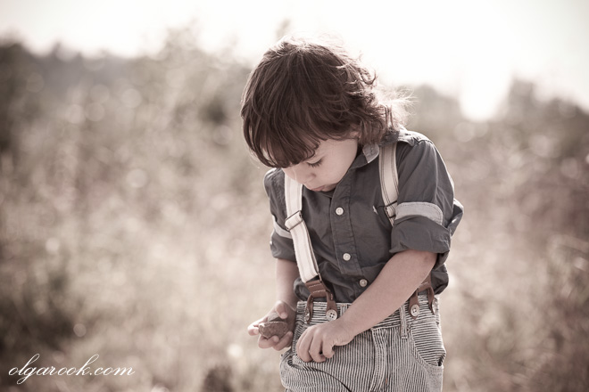 Vintage-like photo of a little boy filling his pocket with stones