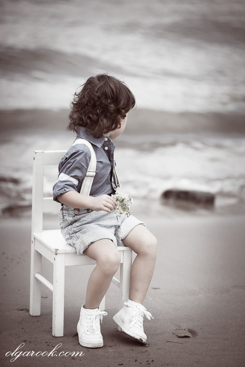 Timeless portrait of a child sitting at a river bank looking at the waves