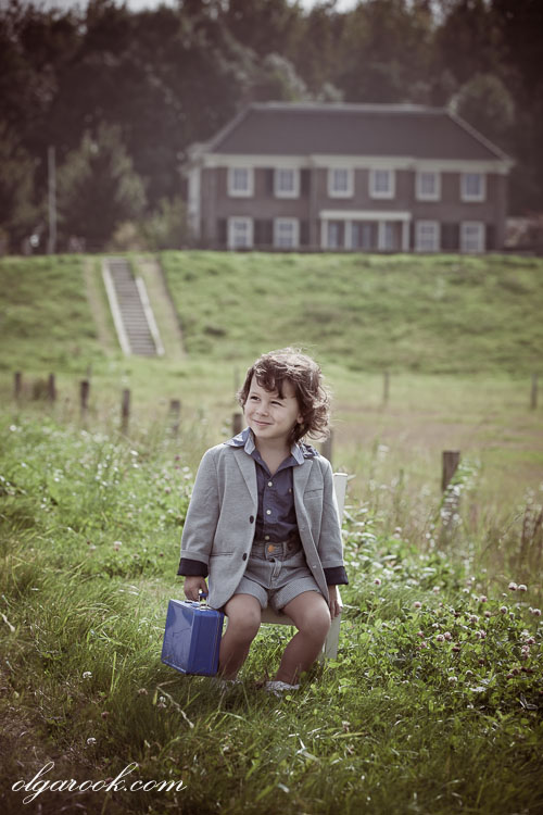 A nostalgic retro style portrait of a little boy sitting on a chair in a field with a mansion behind him.