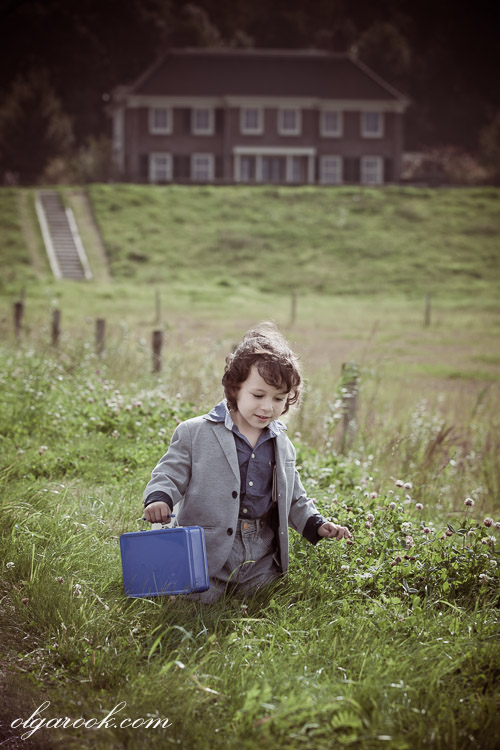 A retro-like photo of a little boy walking through a field. In the background there is an old mansion. The atmosphere and the muted colors add a vintage feel to the image.